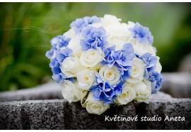 Svatební kytice z cca 24ks bílých růží doplněna trsy modré hortenzie, podložená nevěstiným závojem. 1300,-